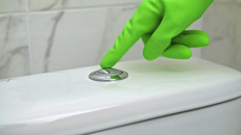 Man With green Glove on Hand Push Basin Mechanism Button for Toilet Water Flush Live Action