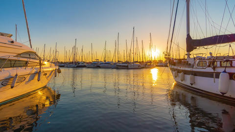Time Lapse. Sunset scene at marina with yachts tied to the docks, sun and sky Footage