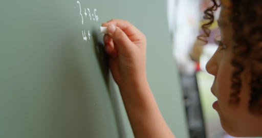 Side view of mixed-race schoolgirl solving math problem on chalkboard in classroom at school 4k Live Action