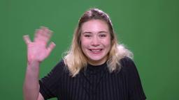 Closeup portrait of young pretty blonde caucasian female waving hi smiling Footage