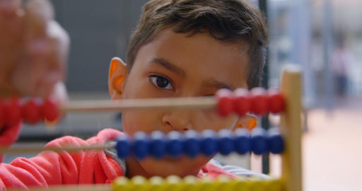 Front view of Asian schoolboy solving math problem with abacus at desk in a classroom at school 4k Live Action