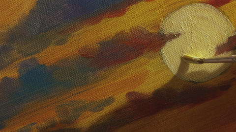 Artist's hand holding fine brush is painting white sun in yellow and red sky Footage