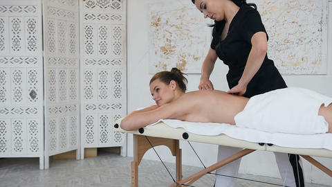 Relaxing young woman relaxing during massage on the back in spa salon Live Action