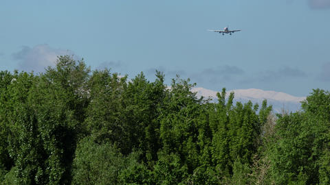 Commercial airplane approaching with beautiful mountains at the background Live Action