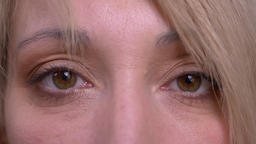 Eye portrait of middle-aged blonde short-haired model watches calmly into camera Footage
