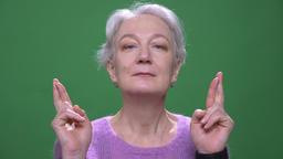 Gray haired grandmother in violet sweater prays with crossed fingers isolated on Footage