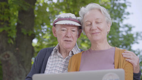 Old woman with grey hair and old man in cap sitting in the bench in the Live Action
