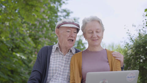 Old woman with grey hair and old man in cap sitting in the bench in the Footage