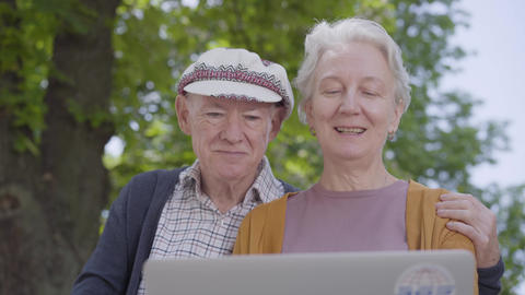 Portrait adorable old woman with grey hair and old man in cap sitting in the Footage