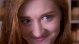 Closeup portrait of young cheerful redhead caucasian female student looking at Footage