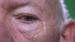 Closeup half face shoot of old senior caucasian male looking at camera with Footage