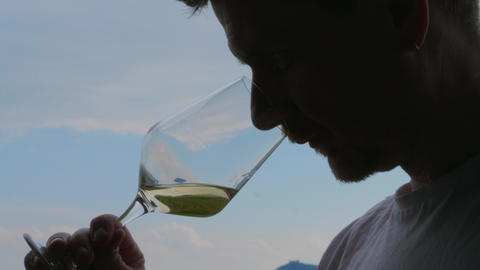 Man swirling, sniffing, tasting white wine against blue sky Live Action