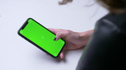 Closeup back view shoot of female hand texting on the phone with green chroma Footage