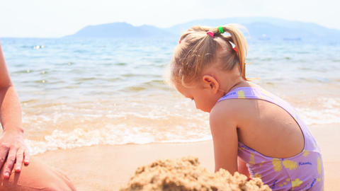 Blond Little Girl Builds Sand Castle on Beach of Azure Sea Footage