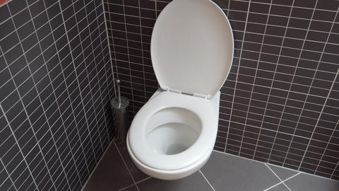 Toilet bowl, lavatory in modern bathroom with black and grey tiles, HD Footage