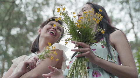 Two beautiful women standing in the forest with amazing wild flowers. Slow Footage