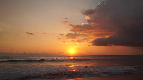 Surfers ride at orange sunset over Indian Ocean Footage