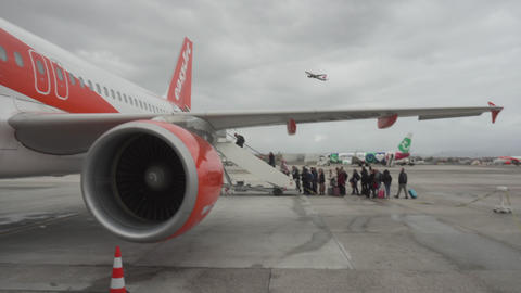 People row boarding the plane and the secod plane takes off Live Action