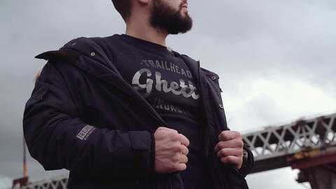 Bearded young man holding jacket on shoulders, looking around Live Action