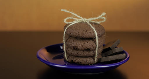 Tasty looking chocolate cookie on a blue plate on dark surface. Warm background Footage