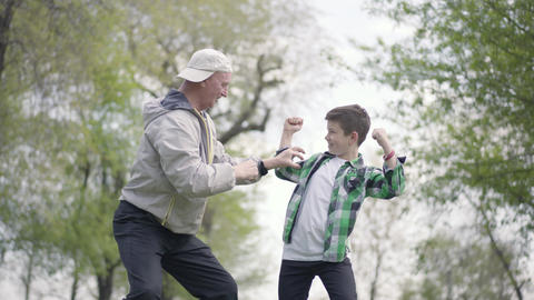 The little boy in a checkered shirt and positive old man showing each other Footage