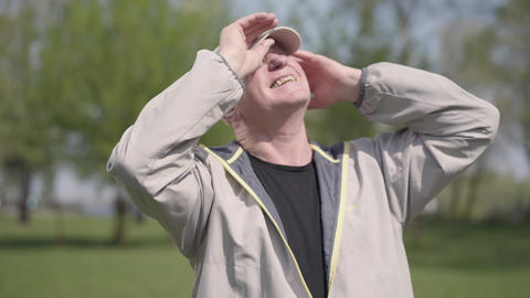 Positive mature man putting the cap on the head, protecting eyes from the sun Footage