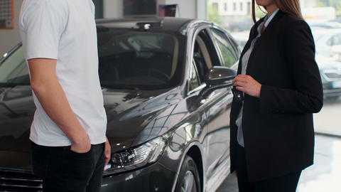 Famale hand gives a car keys to male hand in the car dealership close up Footage