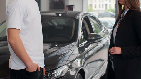 Woman hand gives a car keys to man hand in the car dealership close up Footage