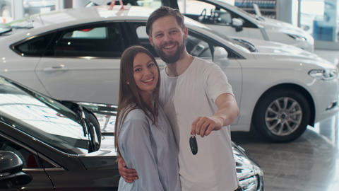 The concept of buying or renting a car. Young happy interracial couple with new Live Action
