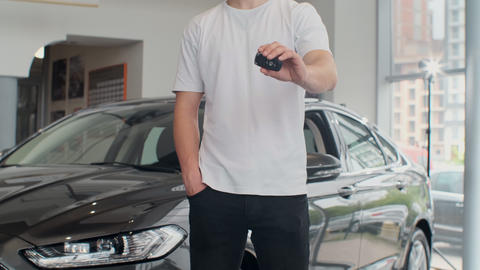 Man customer holding out car keys to his newly bought car. Man holding car keys Live Action