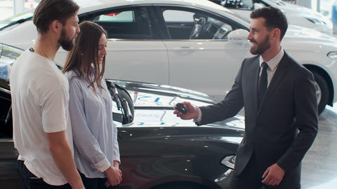 Successful deal between car salesman and young couple in car dealership Live Action