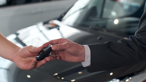 Young man giving keys of car to buyer. Men shaking hands in beautiful car Footage