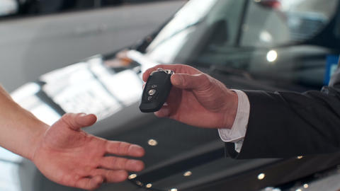 Male hand gives a car keys to man hand in the car dealership close up Footage