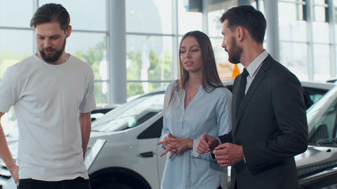 Professional car salesman is telling interested buyers beautiful couple about Live Action