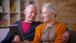 Elderly caucasian spouses watching into tablet and disussing it being positive Footage