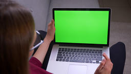 Rear shoot of female freelancer having a videocall on laptop with green chroma Footage