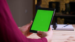 Female hands holding vertically tablet with green chroma screen in office Footage