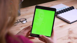 Female hands holding vertically tablet with green chroma screen on office Footage