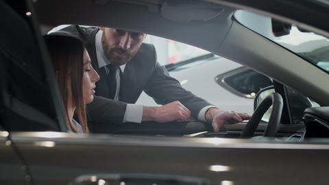 Salesman shows the car features for client. The car is new. Salesman do the best Live Action