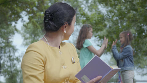 Portrait of an elegant senior woman reading the book in the park in the Footage