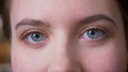 Closeup portrait of young attractive caucasian female face with eyes looking at Footage
