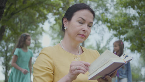 Portrait of an elegant senior woman reading the book in the park in foreground Footage