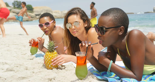 Side view of mixed-race female friends drinking cocktail drinks on the beach 4k Live Action