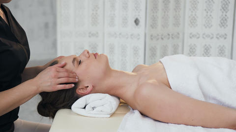 Relaxing young woman having massage on the face in the massage salon Footage
