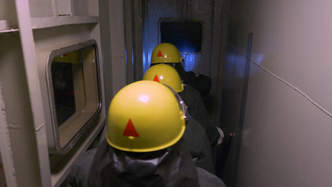 Rescue operation in dark tunnel, back view of rescures in protective suits and Footage