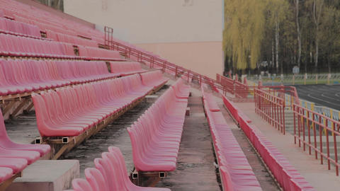 The girl runs in the stadium among the seats, training in the fresh air Live Action