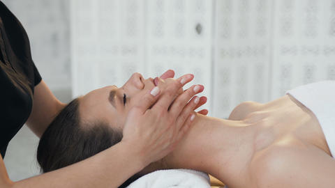 Cute handsome woman during massage on the face in the massage salon Footage