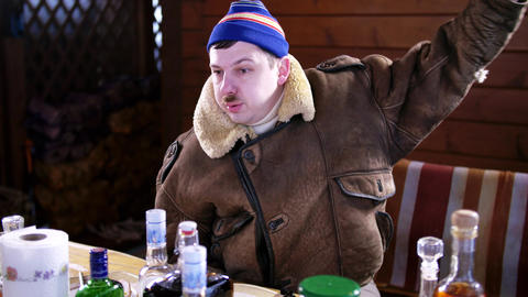 Mature caucasian drunk man with mustache in blue hat and coat twitches at table Footage
