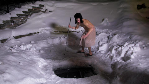 Two naked guys with hats and towels around their waist gathered around ice hole Live Action