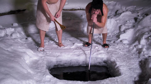 Semi naked guys with towels around their waist put metallic stick into ice hole Live Action